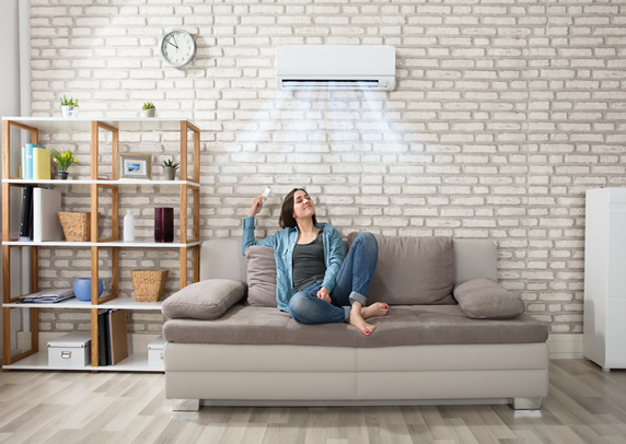 young-woman-holding-remote-control-relaxing-under-the-air-conditioner-609x406